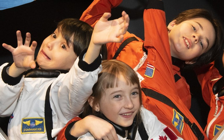 Four young children are dressed in astronaut suits