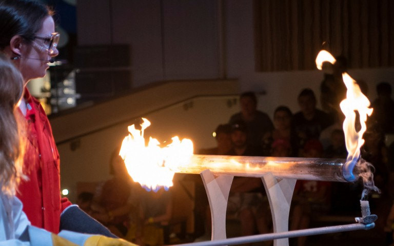 A museum employee wears safety goggles and gloves as she uses a rod as part of a fire demonstration
