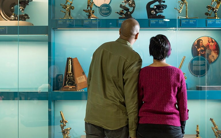 A man and a woman looking at a collection of microscopes