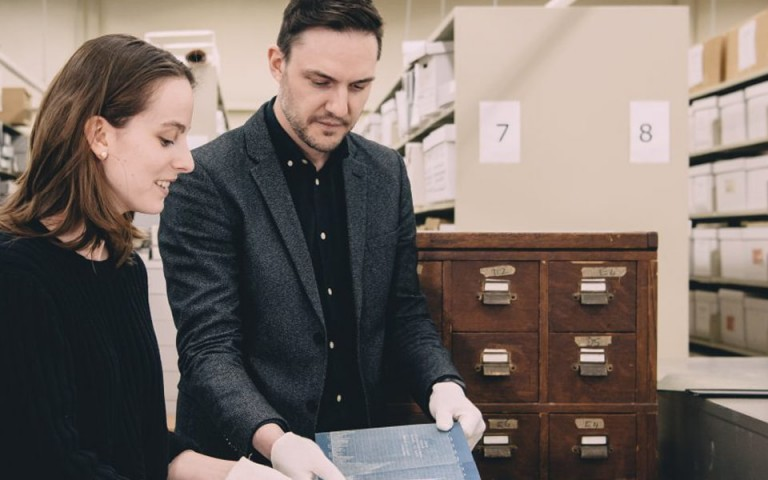 Researchers examine a blueprint in the archival collection