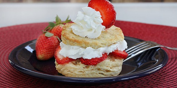 strawberry shortcake with whip cream on top and a slice of strawberry