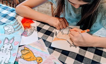 jeune fille qui colore les illustrations d'animaux de la ferme