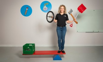A museum employee showing the functionality of a simple machine while holding other simple machines