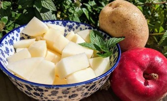 cut up apples and potatos in a bowl