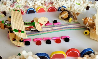A tabletop is filled with edible treats; in the centre, aircrafts are made of cookies, icing, and candy.