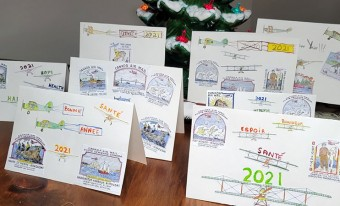 Eight brightly-coloured holiday cards are arranged on a wooden tabletop; each card features different aviation-themed images. Christmas décor is visible in the foreground and background of the image.