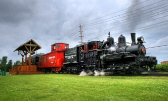 A black steam locomotive pulls away from a wooden platform, with a red and a black rail car in tow