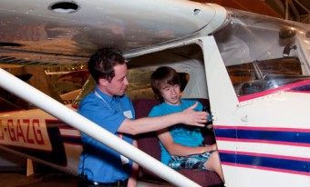A museum employee showing the cockpit of an aircraft to a visiting child