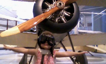 A child dressed like a pilot playing in front of an airplane in the museum