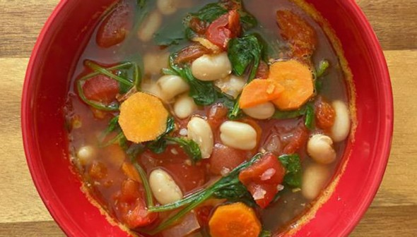 A red soup bowl sits on a wooden cutting board. The bowl is filled with soup that features spinach, tomatoes, white beans, and carrots.