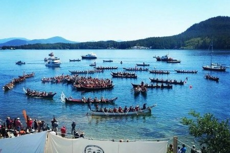 Canoes hover around a beach shore in Bella Bella, British Columbia during the Qatuwas in 2014