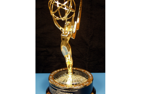 A shiny Emmy award sits on a blue table.