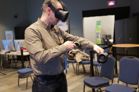 A man tries out virtual reality glasses and holds a controller.