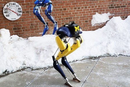 Two pairs of robotic legs are pictured next to a snowbank and a thermometer.