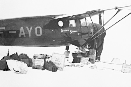 Supplies on snow in front of Dominion Skyways airplane