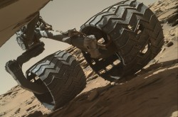 A close up of the Curiosity rover's wheels, showing holes and tears from traversing sharp rocks.