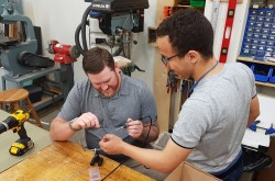 Jason helping Mohamed with soldering to a sensor