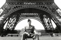 A man in uniform sits in front of the Eiffel Tower.