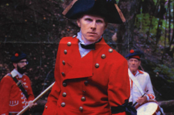 A young man poses as James Wolfe, dressed in historical dress including a red jacket and black hat.