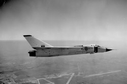 A black-and-white image of a plane in flight.
