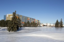 A snowy landscape with a large building — the Collections Conservation Centre — under construction in the distance.