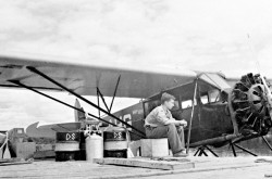 Ken Molson sitting on a dock near a seaplane