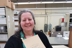 Photograph of archives clerk Sian Jones with a report from the Canada Pacific Steamships fonds