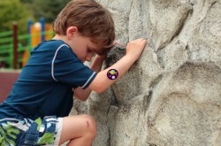Image of child rock climbing outside