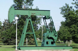 An oil pump jack in a green field.