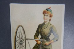 "A woman doing a trick on a modified ""safety"" high wheel bicycle"