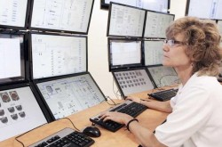 NuScale SMR control room: operator looking at one set of pannels in a 12-reactor plant