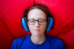 A young girl wearing headphones closes her eyes as she rests on a red cushion.