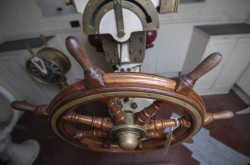 A view of the solid-looking, wooden steering wheel, inside the pilot house from the SS Prince Edward Island.