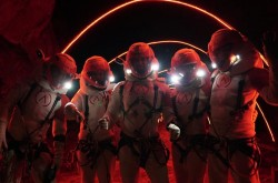 A group of people wearing spacesuits stand in a room illuminated by a red light.