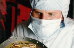 a scientist in clean-room clothing holding a CCD sensor that was installed on the Hubble Space Telescope