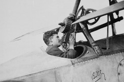 A black-and-white image of William Avery Bishop in the cockpit of a Nieuport aircraft, handling a machine gun.