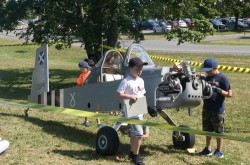 Three children with notebooks study a small plane that is taped off.