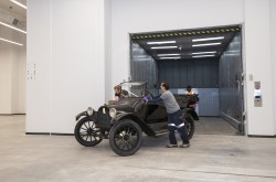 Two men wearing artifact gloves move a vintage black car off an oversized elevator.