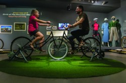 Two people sit on bikes in the middle of a museum display.