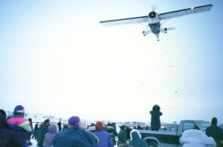 A group of people stand outdoors, looking up as a small white plane drops candy and gifts while it flies over the crowd.
