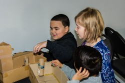 Three children designing and building their own cardboard games
