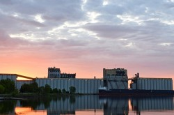 A ship in front of a large grain elevator; the sun rises in the background.