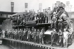 Image is a black-and-white photograph showing employees standing on and around a steam locomotive. There are about 40 men