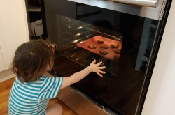 A young child watches cookies bake in an oven.