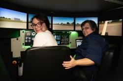 Two women smile as they turn to face the camera; they're sitting inside a flight simulator.