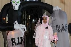 A young girl in a pink outfit and matching hijab wears a set of butterfly wings as she poses in front of a Halloween display.
