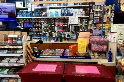 A checkout counter at a pharmacy; several red plastic boxes with a pink notice indicate that customers should not move the barrier in order to protect the safety of the staff, and a plexiglass sheet is suspended to separate customers and check out staff.