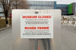 "A sign in front of the barricaded museum buildings reads: ""MUSEUM CLOSED…Access beyond this point is restricted to on-duty essential personnel only."""