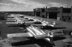 A black-and-white photograph showing a line of CF-100 jet aircraft in front of two hangars.
