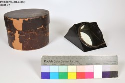 A small metal and glass prism and its old brown storage box sit on a white background. A Kodak color strip sits in front of the artifacts.